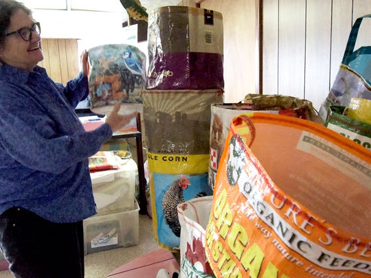 Artist Mary Magenta stacks some of the bags she'd created from used feed bags outside her New Freedom home Tuesday, Nov. 21, 2017. The mixed-media artist has found a niche with repurposing the material into various sized bags for a multitude of uses. Bill Kalina photo
