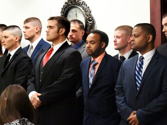 Probationary police officers await the swearing-in