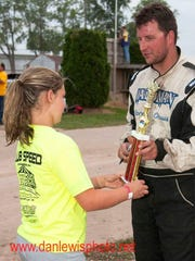 Green Bay driver Benji LaCrosse gives his trophy away to a girl after winning his 100th career IMCA modified feature July 12 at Seymour Speedway.