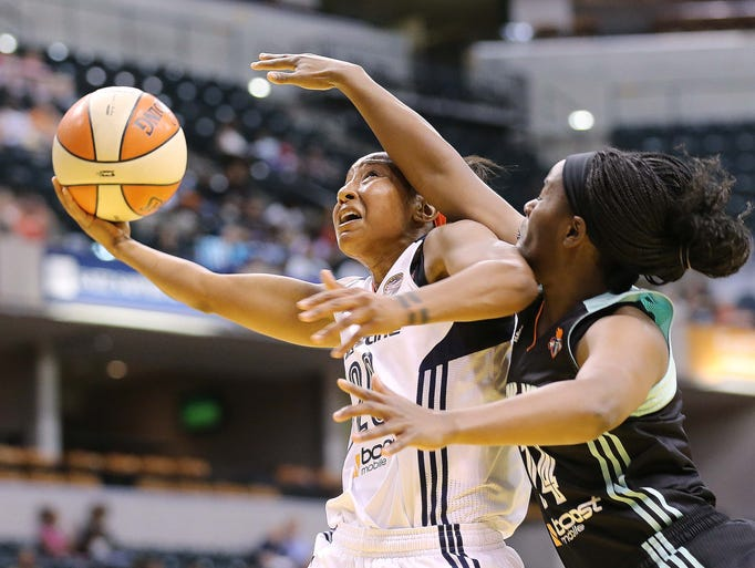 Briann January of the Fever is fouled by Liberty defender Sugar Rodgers. The Indiana Fever hosted the New York Liberty in WNBA action at Bankers Life Fieldhouse Saturday May 31, 2014.