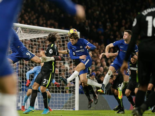 Chelsea's Marcos Alonso, centre, scores a goal during the English Premier League soccer match between Chelsea and Brighton & Hove Albion at Stamford Bridge in London, Tuesday Dec. 26, 2017. (AP Photo/Tim Ireland)