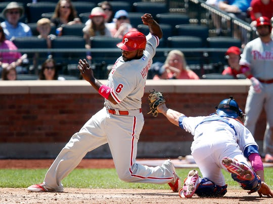 The Phillies' Ryan Howard evades a tag at home by Anthony Recker to score on an RBI single by Domonic Brown during the fourth inning Sunday.