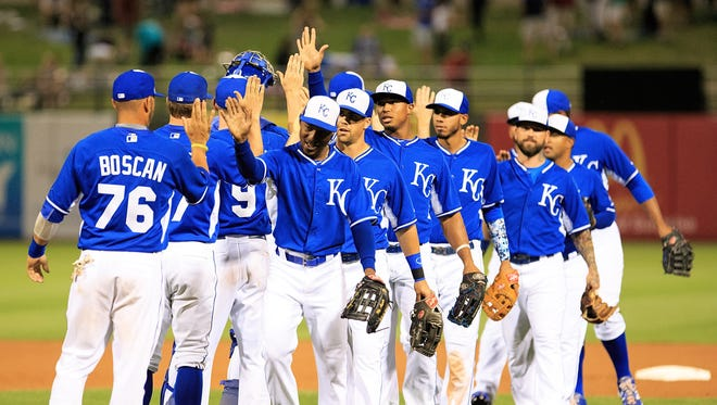 Kansas City Royals players celebrate after defeating the Seattle Mariners during a Cactus League game in Surprise on March 27, 2015.