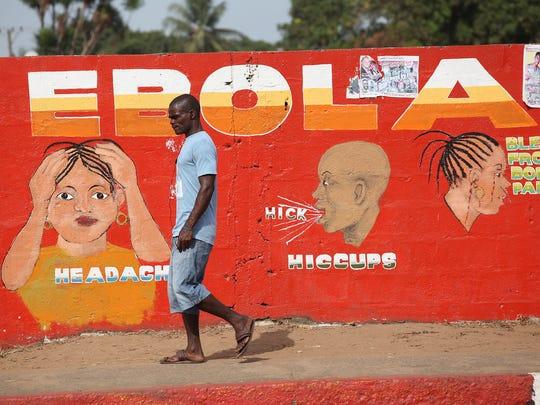 A Liberian man walks by an Ebola awareness painting