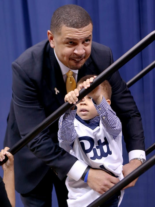 Jeff Capel, top, tucks a Pitt team jersey in on his 5-year-old son, Elijah, during a news conference where he was introduced as the new men's basketball coach for the University of Pittsburgh's NCAA college team, Wednesday, March 28, 2018, in Pittsburgh. Capel was an associate head coach at Duke. He replaces Kevin Stallings. (AP Photo/Keith Srakocic)