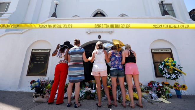 A group of women pray together in front of the Emanuel AME Church on Thursday.