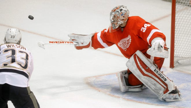 Detroit Red Wings goalie Petr Mrazek (34) knocks the puck away against the Nashville Predators during the third period of an NHL hockey game in Detroit, Saturday, Jan. 17, 2015.  The Red Wings defeated the Predators 5-2.
