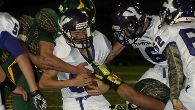 Yerington senior Daniel Sciarani tries to pull away from a Battle Mountain defender who has a hold of his jersey during a 46-23 victory for the Lions.