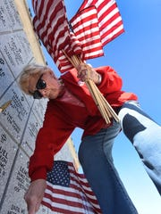 Jean Brown places flags on the graves of local veterans
