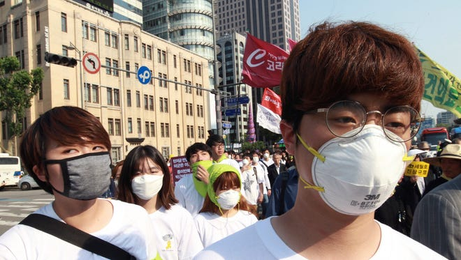 Protesters wear masks as a precaution against the MERS, Middle East Respiratory Syndrome, virus as they march after a rally against government's labor policy in Seoul, South Korea, Sunday, June 7, 2015.