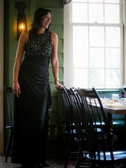Carol Mayhart wears a floor-length gown with lace inset