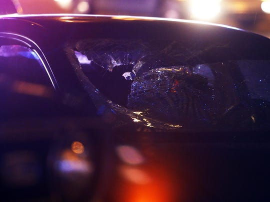 A car with a crumpled windshield sits at the scene as Delaware State Police investigate after a pedestrian was struck by a car on Kirkwood Highway in front of Bull's Eye Saloon and Restaurant shortly after 10 p.m. Wednesday.