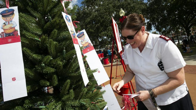 Major Marion Durham puts tags on the Salvation Army's Angel Tree during the 2018 Red Kettle Campaign Kickoff in 2018 on the Ocala downtown square.