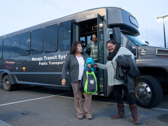 Commuters disembark from a Navajo Transit System bus on Wednesday in the Walmart parking lot on West Main Street in Farmington.