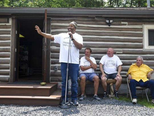 Tim Witherspoon, former world heavyweight boxing champion, talks to the crowd during the June 1 grand opening of Fighter's Heaven, Muhammad Ali's Training Camp, in Deer Lake, Schuylkill County. Witherspoon was a sparring partner for Ali. Looking on are Sam Matta, camp manager and media relations, left, Mike Madden, owner of Fighter's Heaven, center, and Gene Kilroy, right. Kilroy was Ali's business manager and close friend. The building in background was Ali's kitchen.