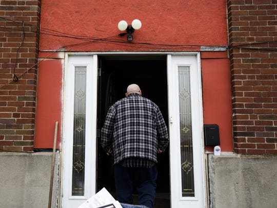 Darrell Whisman walks into a front door he added to