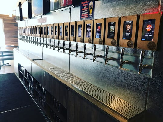 A beer wall at PizzaRev where customers pour their
