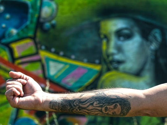 Twisted Tatt2's staff Will Melton shows his arm tattoo in front of an adorning mural painted on the building of the tattoo parlor on South Broadway in Camden.