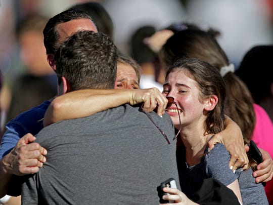 A family reunites following a shooting at Marjory Stoneman Douglas High School in Parkland, Florida, on Feb. 14, 2018.