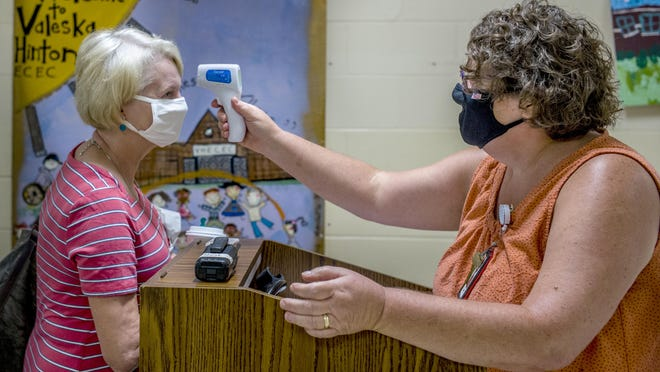 Valeska Hinton Early Childhood Education Center librarian Kylie Jacob, left, stands for a temperature reading by school nurse Lisa Wiltz on her arrival Wednesday, July 22, 2020 for the first school opening in Peoria Public Schools district.