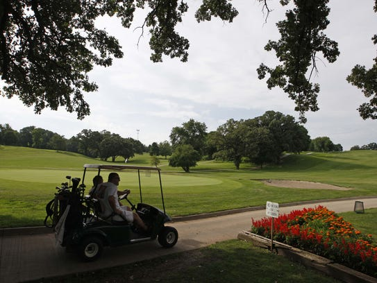 Players drive off after teeing off on the first hole