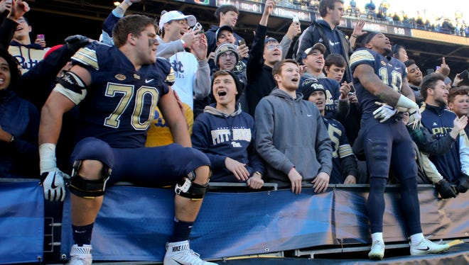 Pittsburgh offensive tackle Brian O'Neill (70) and wideout/returnman Quadree Henderson (10) celebrate with fans in the student section after Pitt upset No. 2-ranked Miami Saturday.