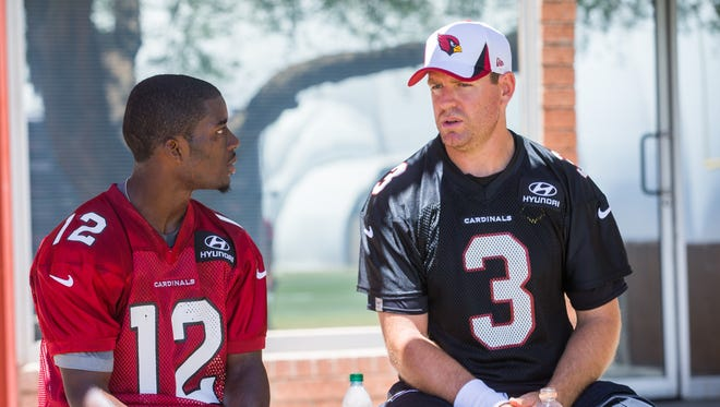 Wide receiver John Brown, left, talks with quarterback Carson Palmer after practice at the Arizona Cardinals Training Facility in Tempe on Tuesday, May 20, 2014.