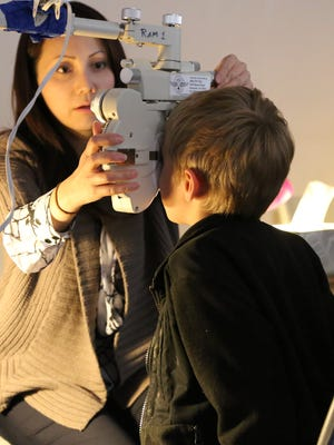 A woman sets up equipment to look at a boy's eyes during a Remote Area Medical clinic. RAM, an internationally known organization providing free medical care, will host a clinic Dec. 3-4 at Milton High School.