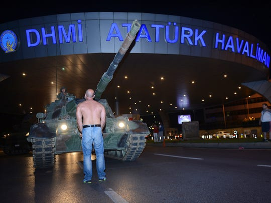 A man stands in front of a tank in the entrance to