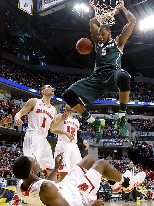 Michigan State forward Adreian Payne (5) dunks over Wisconsin forward Nigel Hayes, bottom, in the first half of an NCAA college basketball game in the semifinals of the Big Ten Conference tournament Saturday, March 15, 2014, in Indianapolis. (AP Photo/Michael Conroy)