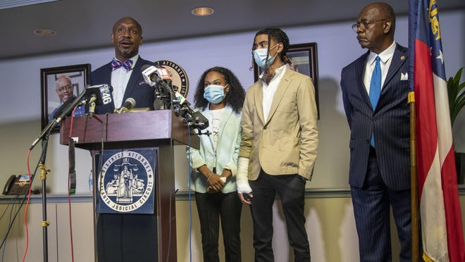 Attorney Mawuli Davis, left, speaks on behalf of Taniyah Pilgrim, center, and Messiah Young, right, during a press conference by the Fulton County District Attorney's Office in Atlanta, Monday, June 2, 2020. Six Atlanta police officers have been charged after a dramatic video showed authorities pulling the two young people from a car during protests over the death of George Floyd. At right is Fulton County District Attorney Paul Howard.