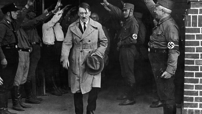 In this Dec. 5, 1931 file photo, Adolf Hitler, leader of the National Socialists, is saluted as he leaves the party's Munich headquarters. In Munich, Hitler launched his political career with speeches condemning Jews and proclaiming the ethnic superiority of Germans.