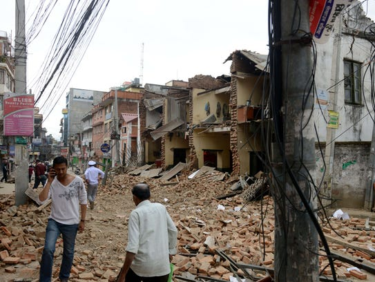 Nepalese walk past collapsed buildings at Lalitpur,