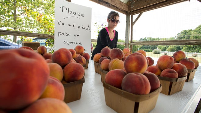 Peaches are arranged for sale by Kenzie Wilcox at Garden of Eden in Salisbury, Maryland.