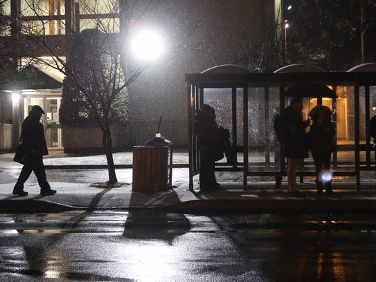 Commuters wait under a bus shelter during light snow