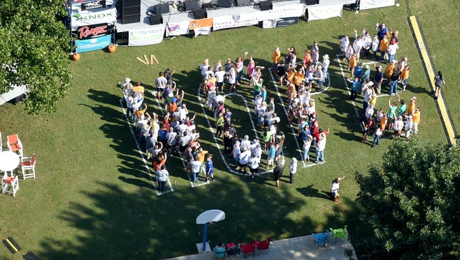 Seen from an Air Evac helicopter flying above, attendees of the sixth annual Bridge Bash spell out the word 'hope' at Big Spring Park in Cotter on Saturday. The event saw volunteers package 100,000 meals for the hungry.