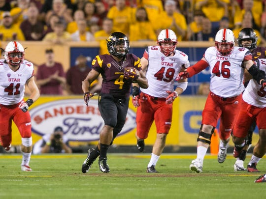 ASU running back Demario Richard carries the ball in front of a host of Utah defenders during the first quarter at Sun Devil Stadium in Tempe on Saturday, Nov. 1, 2014.
