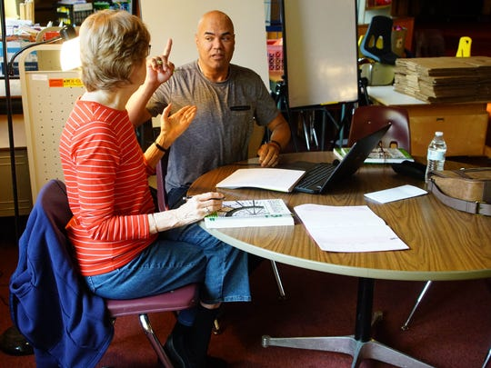 Judy Crescenzi, a volunteer with Literacy Delaware, works with Esneyder Lopez on improving his English language skills.