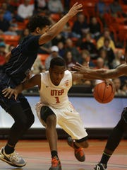 UTEP's Dominic Artis, center, dribbles between Rice defenders Connor Cashaw, left, and Bishop Mency during the first half Friday. The Miners won the Conference USA opener 61-60.