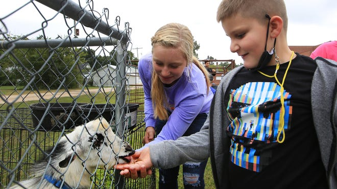 Haven Grade schooler Atticus Schultz laughs as a Pygmy goat takes feed out of his hand as Haven High School FFA member Brie Brawner, 15, helps him Wednesday morning at the Farm Safety Day 2020 event. About 250 students in grades pre-k through 4th grade were able to visit 10 different stations for 10 minutes each, learning about the care of animals and safety measures to be followed around them and farm equipment.