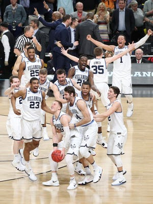 Villanova players celebrate with teammates after defeating Michigan to win the national title in the 2018 NCAA tournament.