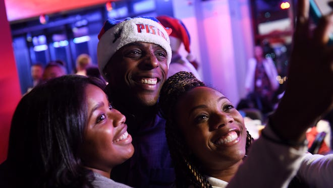 La'Chattie Smith and Ree Frazier, right, of the Empowerment Plan take a selfie with Pistons forward Anthony Tolliver at the event.