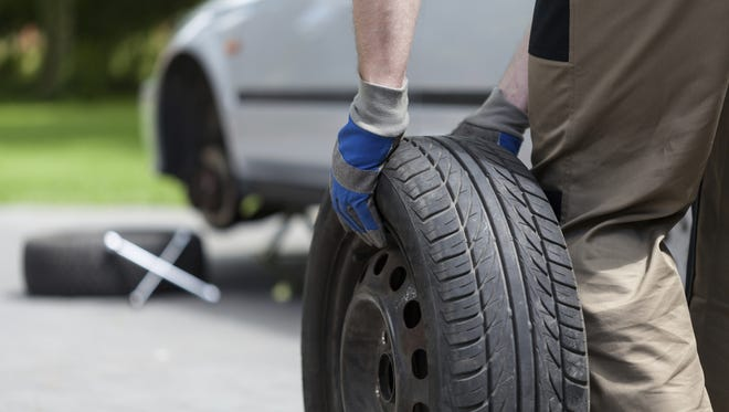 File: Man rolling a spare wheel.