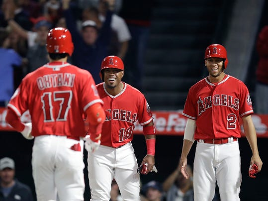 Los Angeles Angels' Luis Valbuena, center, and Andrelton Simmons, right, stand near the home plate to greet Shohei Ohtani, of Japan, after Ohtani hit a three-run home run during the first inning of a baseball game against the Cleveland Indians, Tuesday, April 3, 2018, in Anaheim, Calif. (AP Photo/Jae C. Hong)