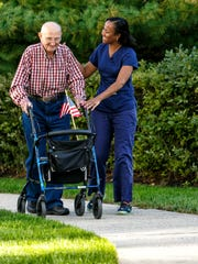 A home health aide helps a man with a patriotic walker, in this image supplied by Hackensack Meridian Health.