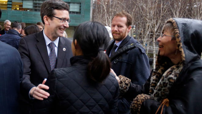 Washington Attorney General Bob Ferguson, left, is greeted by well-wishers after he spoke to reporters Friday, Feb. 3, 2017, following a hearing in federal court in Seattle. A U.S. judge on Friday temporarily blocked President Donald Trump's ban on people from seven predominantly Muslim countries from entering the United States after Washington state and Minnesota urged a nationwide hold on the executive order that has launched legal battles across the country. (AP Photo/Ted S. Warren)
