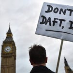 A protester opposed to British military action in Syria holds a placard reading 'Don't be daft, Dave!' outside the Houses of Parliament in London on Dec. 1.