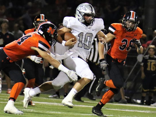 Northville defenders try to slow down Plymouth quarterback