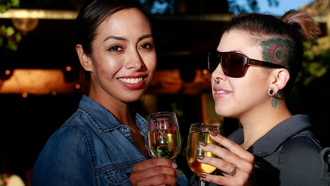 Dusti Monge, left, and Stephanie Bushman, of Farmington, pose with their wine glasses during the Harvest Wine Festival on Saturday at Wines of the San Juan in Blanco.