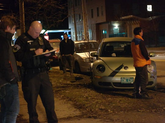 Police and residents in Burlington look over several cars damaged late Thursday in a hit-and-run in the city near the intersection of North Avenue and North Street.